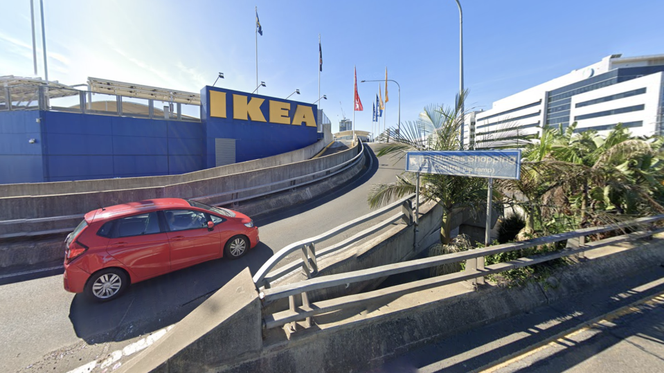 Pictured is a red car driving up a ramp towards IKEA and Rhodes Shopping Centre in Sydney.