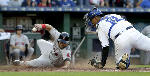 Boston Red Sox's Mitch Moreland beats the tag by Kansas City Royals catcher Salvador Perez to score on a three-run double by Xander Bogaerts during the fifth inning of a baseball game Saturday, July 7, 2018, in Kansas City, Mo. (AP Photo/Charlie Riedel)