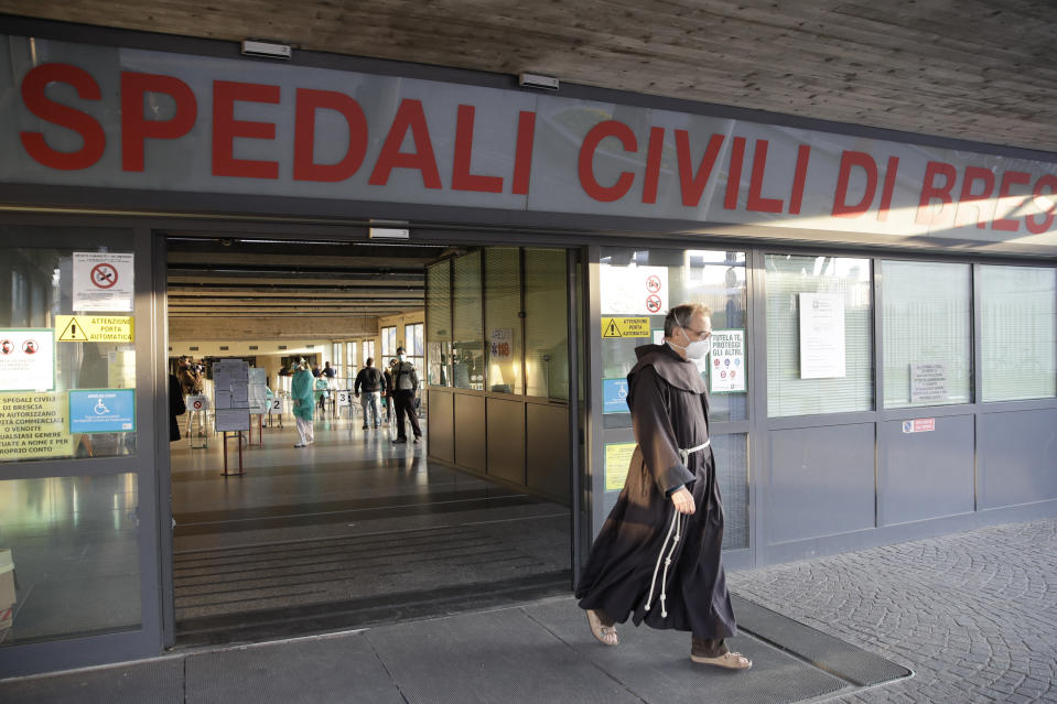 A friar walks out of the Brescia Spedali Civili hospital, Italy, Monday, March 16, 2020. For most people, the new coronavirus causes only mild or moderate symptoms. For some, it can cause more severe illness, especially in older adults and people with existing health problems. (AP Photo/Luca Bruno)