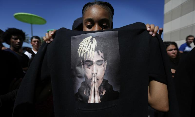 A fan holds a sweatshirt bearing an image of the rapper at the public memorial service in Florida.