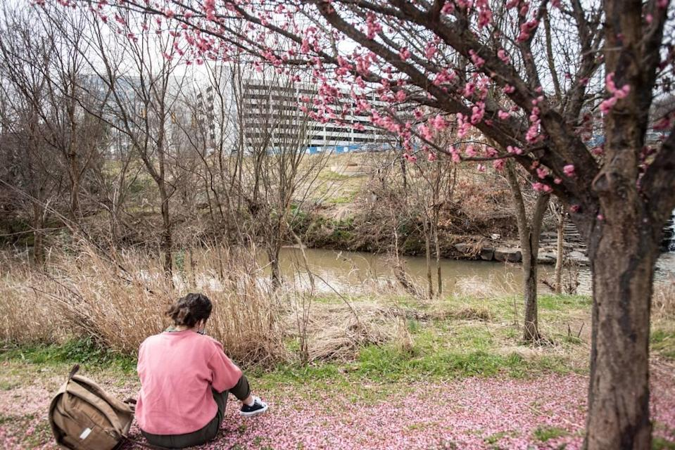 A woman sits by a Sugar Creek in Charlotte, NC, on Saturday, February 25, 2021.