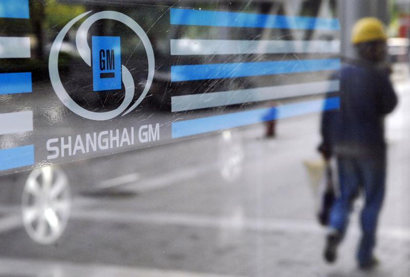 A labourer is reflected in the glass of a Shanghai General Motors exhibition hall in Shanghai