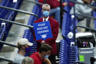 FILE - In this March 21, 2021, file photo, an usher holds a sign reminding fans to wear masks during a college basketball game between Houston and Rutgers in the second round of the NCAA tournament at Lucas Oil Stadium in Indianapolis. President Joe Biden's pleas for states to stick with mask mandates to slow the spread of the coronavirus were being largely ignored Tuesday, March 30, as several Republican governors stayed on track to drop the requirement in their states. (AP Photo/Mark Humphrey, File)