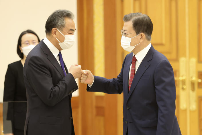 South Korean President Moon Jae-in, right, greets with Chinese Foreign Minister Wang Yi prior to a meeting at the presidential Blue House in Seoul, South Korea, Wednesday, Sept. 15, 2021. Wang was to hold a meeting with his South Korean counterpart for talks expected to focus on North Korea and other regional security issues. (Choi Jae-ku/Yonhap via AP)