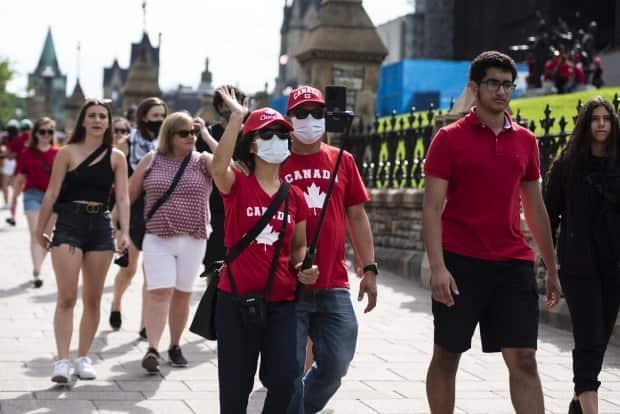 People wear masks and the maple leaf as they walk along Wellington Street in Ottawa on Canada Day.  (Justin Tang/The Canadian Press - image credit)