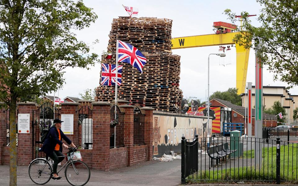 A woman cycles past a bonfire on the Newtownards Road in Belfast as preparations are underway for the July 11th loyalist bonfires - PA