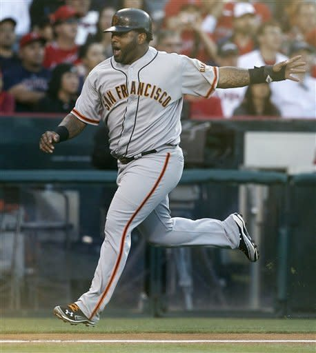 San Francisco Giants' Pablo Sandoval reacts as he scores on a two run-triple by Brandon Crawford against the Los Angeles Angels during the second inning of a baseball game in Anaheim, Calif., Monday, June 18, 2012. (AP Photo/Chris Carlson)