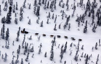 FILE - In this March 11, 2009, file photo, Matt Hayashida of Willow, Alaska, drives his team alone the Iditarod Trail Sled Dog Race trail near the Takotna, Alaska checkpoint. Technology is used to track Alaska's Iditarod Trail Sled Dog Race far from the competitors tackling the off-the-grid route. Fifty-one mushers as of Friday, March 8, 2019, are traveling long stretches between remote village checkpoints with no other company but the dogs pulling their sleds. (AP Photo/Al Grillo, File)