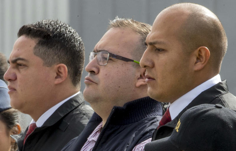 Mexico's former Veracruz state Gov. Javier Duarte, center, is escorted by police to an aircraft as he is extradited to Mexico City, at an Air Force base in Guatemala City, Monday, July 17, 2017. Duarte faces charges of embezzlement and ties to organized crime in his home country. (AP Photo/Moises Castillo)