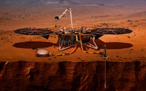 This illustration made available by NASA in 2018 shows the InSight lander drilling into the surface of Mars - Credit: AP