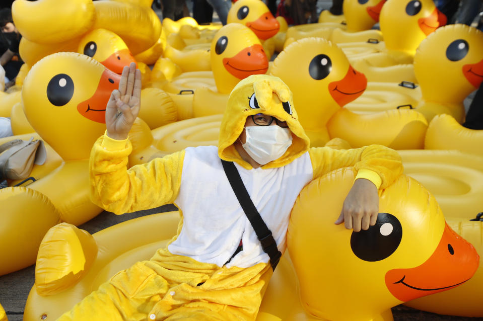 A protester flashes the three-finger protest gesture while wearing an outfit of a yellow duck, which has become a good-humored symbol of resistance during anti-government rallies, Wednesday, Nov. 25, 2020, in Bangkok, Thailand. Thai authorities have escalated their legal battle against the students leading pro-democracy protests, charging 12 of them with violating a harsh law against defaming the monarchy. (AP Photo/Sakchai Lalit)