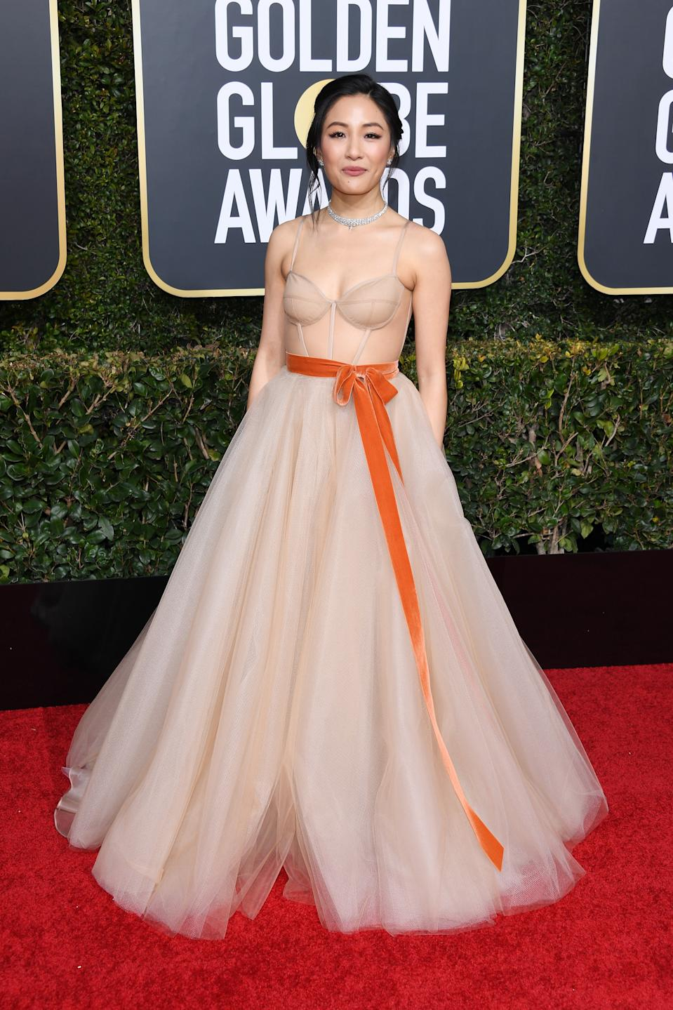 <p>After becoming the first Asian American woman to be nominated for an award in decades, Constance Wu showed up to the 2019 Golden Globes dressed to impress in this nude coloured tulle princess gown, with an orange accent ribbon around the waist. (Image via Getty Images)</p>