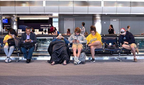 PHOTO: In this June 12, 2019, file photo, passengers waiting for their flight to board sit in the terminal and use their smartphones at Denver International Airport in Denver. (Robert Alexander/Getty Images, FILE)