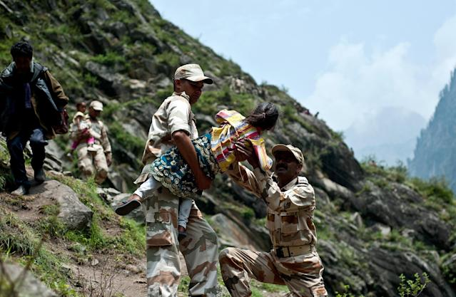 Indo-Tibetan Border Police personnel carry a child as they provide rescue assistance for stranded Indian pilgrims after a section of road was washed away in Govind Ghat on June 23, 2013. Bad weather hampered rescue operations June 23 in northern India where up to 1,000 people are feared to have died in landslides and flash floods that have left pilgrims and tourists stranded without food or water. AFP PHOTO/MANAN VATSYAYANA