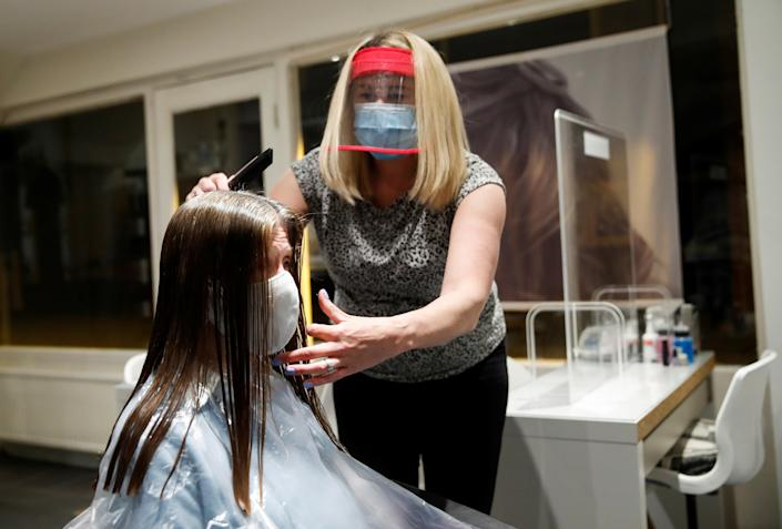 Kelly Boad, owner of Hair & Beauty Gallery, gives Sue Butcher a haircut as non-essential businesses reopen as coronavirus disease (COVID-19) lockdown restrictions begin to ease in Warwick, Britain, early April 12, 2021. REUTERS/Andrew Boyers