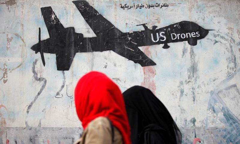 Women walk past graffiti in Yemen, parts of which are the first 'temporary' battlefield designations. Under Obama, the president and his counter-terrorism adviser played a big role in authorizing attacks on suspected terrorists.