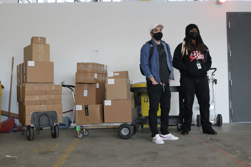 Nabis delivery specialists Daniel Avina and Tyler Hattix wait next to a shipment of cannabis products at the Nabis warehouse in Oakland,