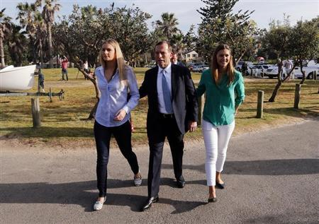 Abbott, who leads the conservative opposition, arrives with his daughters Bridget and Frances to cast his vote on election day at the Freshwater Beach Surf Lifesaving Club in Sydney