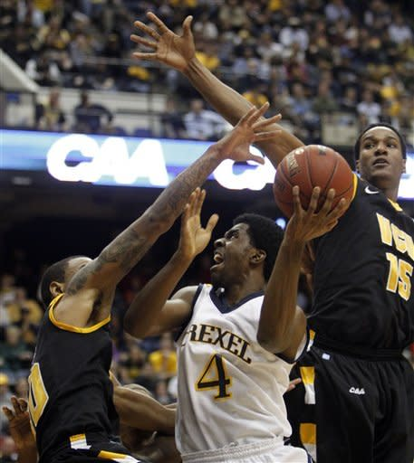 Drexel guard Frantz Massenat (4) dries to the basket as Virginia Commonwealth forward Juvonte Reddic (15) and Virginia Commonwealth guard Darius Theus (10) defend during the first half of the Colonial Athletic Association Championship NCAA college basketball game at the Coliseum in Richmond, Va., Monday, March 5, 2012. (AP Photo/Steve Helber)