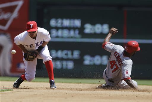 Texas Rangers second baseman Ian Kinsler (5) is unable to handle the throw from catcher A.J. Pierzynski as Los Angeles Angels' Howard Kendrick (47) reaches safely on a steal in the second inning of a baseball game Friday, April 5, 2013, in Arlington, Texas. (AP Photo/Tony Gutierrez)