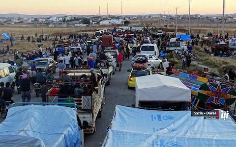People in their vehicles who fled from Daraa in late June gathering near the Syria-Jordan border - Credit: Nabaa Media