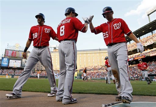 Washington Nationals' Michael Morse, left, and Adam LaRoche, right, fist-bump Danny Espinosa after scoring on a single by Xavier Nady in the second inning of an interleague baseball game against the Baltimore Orioles in Baltimore, Saturday, June 23, 2012. (AP Photo/Patrick Semansky)