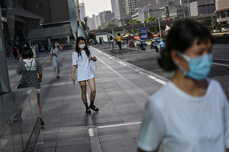 Women wearing a face mask walk in a street of Wuhan, in Chinas central Hubei province on May 18, 2020. - Authorities in the pandemic ground zero city of Wuhan have ordered mass COVID-19 testing for all 11 million residents after a new cluster of cases emerged over the weekend. (Photo by Hector RETAMAL / AFP) (Photo by HECTOR RETAMAL/AFP via Getty Images)