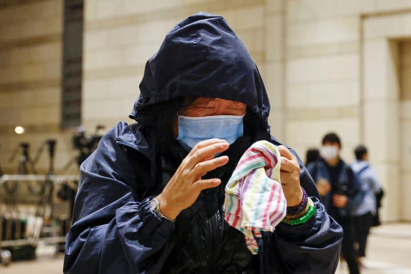 Supporter of pro-democracy activist cries after court grants bail to 15 of 47 democracy activists charged with subversion over national security law at West Kowloon Magistrates' Courts, in Hong Kong