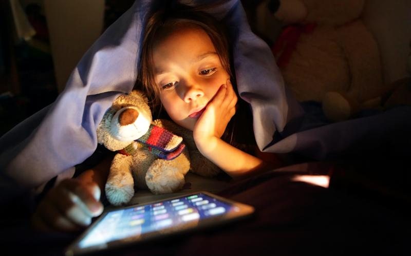 A young girl being kept awake by using a tablet at night - PeterCade
