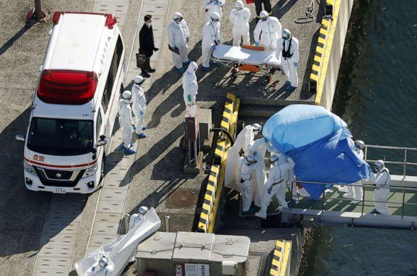 PHOTO: Officers in protective gear escort a person (under the blue sheet) who was on board the Diamond Princess cruise ship and tested positive for the new coronavirus, in Yokohama, Japan, Feb. 4, 2020. (Kyodo Kyodo/Reuters)