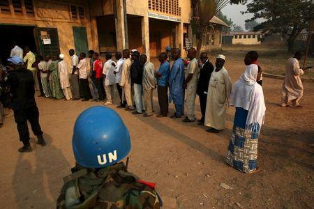 A United Nations security officer keeps guard as people wait in line to cast their votes during the second round of presidential and legislative elections in the mostly Muslim PK5 neighbourhood of Bangui, Central African Republic