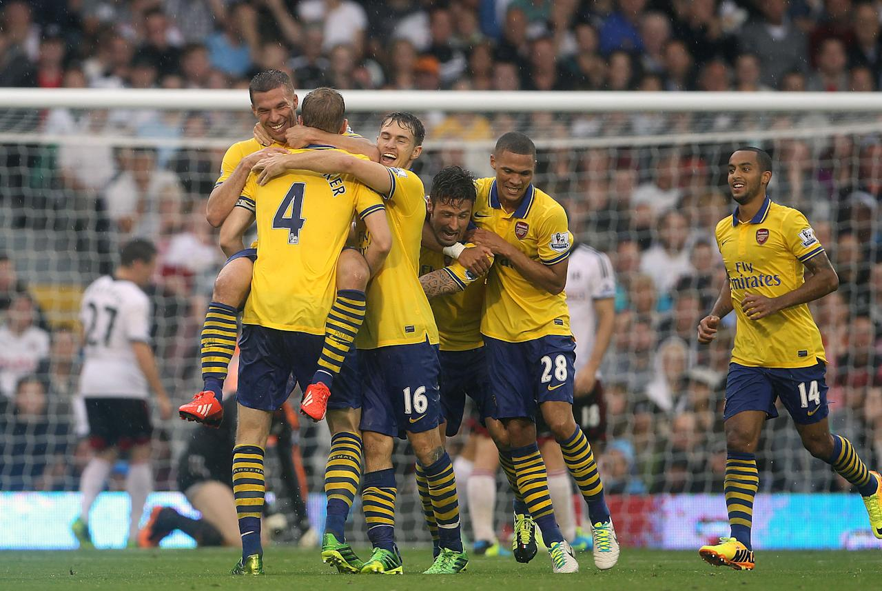 Arsenal's Lukas Podolski celebrates his first goal during the Barclays Premier League match at Craven Cottage, London.