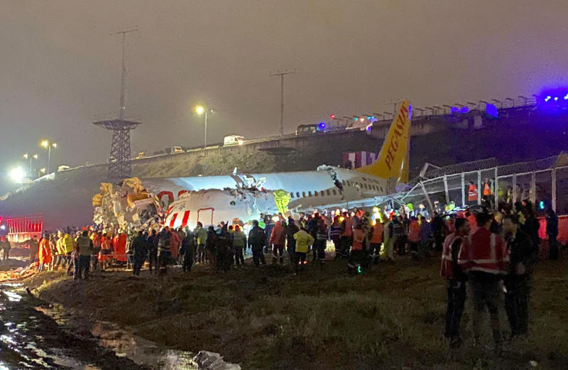 Rescue members and firefighters work after a plane skidded off the runway at Istanbul's Sabiha Gokcen Airport