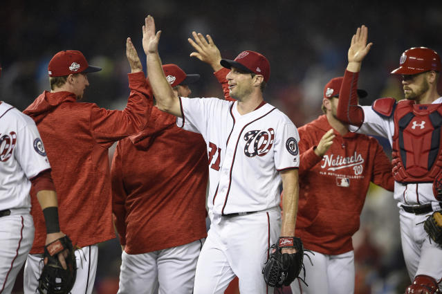 Washington Nationals' Max Scherzer, center, celebrates with his teammates after the first baseball game of a doubleheader against the Chicago Cubs, Saturday, Sept. 8, 2018, in Washington. Scherzer threw a complete game. (AP Photo/Nick Wass)