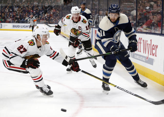 Columbus Blue Jackets forward Kevin Stenlund, right, of Sweden, passes the puck in front of Chicago Blackhawks defenseman Adam Boqvist, left, of Sweden, and forward Jonathan Toews during the second period of an NHL hockey game in Columbus, Ohio, Sunday, Dec. 29, 2019. (AP Photo/Paul Vernon)