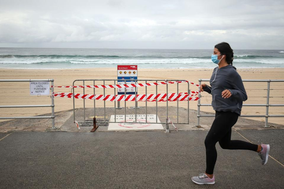 A jogger wearing a protective mask runs past a notice of closure and a barrier in front of an entrance to Bondi Beach in Sydney.