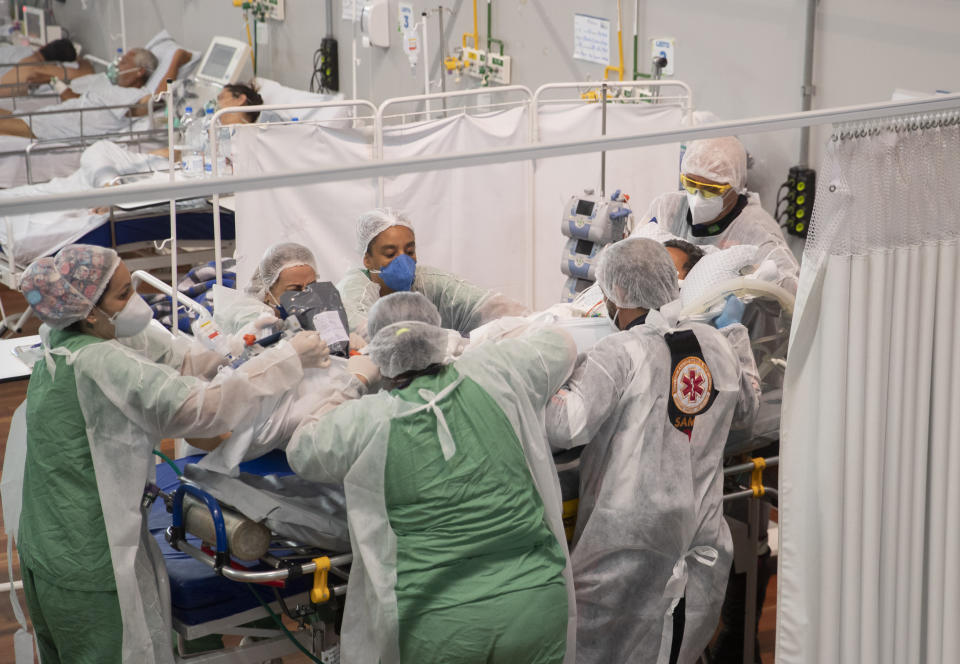 Health workers treat a COVID-19 patient in the ICU of a field hospital built inside a gym in Santo Andre, on the outskirts of Sao Paulo, Brazil, Thursday, March 4, 2021. (AP Photo/Andre Penner)