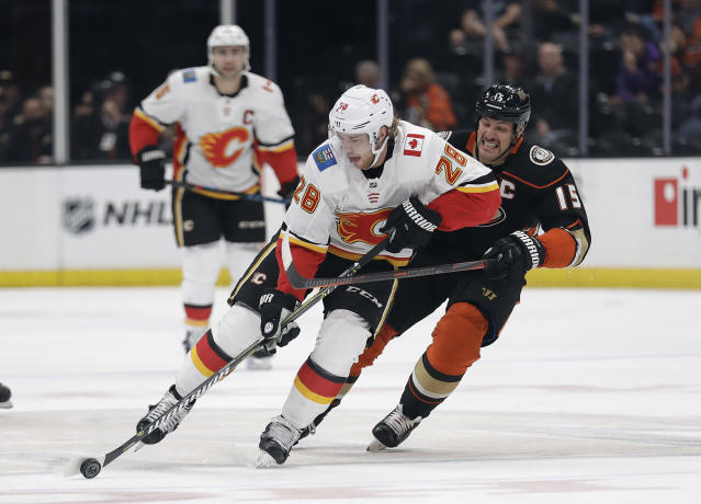 Calgary Flames' Elias Lindholm (28) is defended by Anaheim Ducks' Ryan Getzlaf during the first period of an NHL hockey game Wednesday, Nov. 7, 2018, in Anaheim, Calif. (AP Photo/Marcio Jose Sanchez)