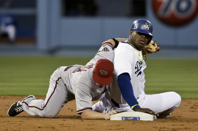 Los Angeles Dodgers' Yasiel Puig, right, is safe under the tag by Arizona Diamondbacks second baseman Aaron Hill after stealing during second inning of a baseball in Los Angeles, Friday, April 18, 2014. (AP Photo/Chris Carlson)