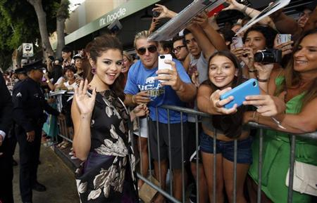"""Cast member Selena Gomez waves while greeting fans at the premiere of """"Getaway"""" in Los Angeles, California August 26, 2013. REUTERS/Mario Anzuoni"""