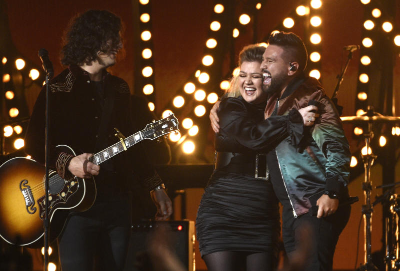 """Dan Smyers, left, and Shay Mooney, right, of Dan + Shay, and Kelly Clarkson react after performing """"Keeping Score"""" at the 54th annual Academy of Country Music Awards at the MGM Grand Garden Arena on Sunday, April 7, 2019, in Las Vegas. (Photo by Chris Pizzello/Invision/AP)"""