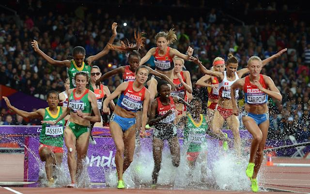 Athletes negotiate a water hazard during the Women's 3000m Steeplechase at the Olympic Games in London, Monday, Aug. 6, 2012. (AAP Image/Dave Hunt) NO ARCHIVING