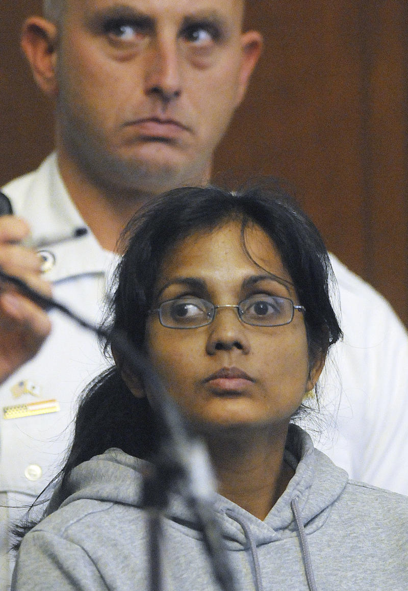 Annie Dookhan, 34, of Franklin, Mass., stands near a court officer during her arraignment Friday, Sept. 28, 2012, in Boston Municipal Court on two counts of obstruction of justice and pretending to hold a degree for a college or university. Dookhan's alleged mishandling of drug samples prompted the shutdown of a state drug lab in Boston in August and resulted in the resignation of three officials, including the state's public health commissioner.  (AP Photo/Boston Herald, Patrick Whittemore, Pool)