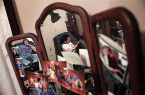 Davy Lin, a foreign exchange student from Taiwan and Kenny Wold, a member of his host family are reflected in a mirror covered in family photos in Revillo, South Dakota February 13, 2012.