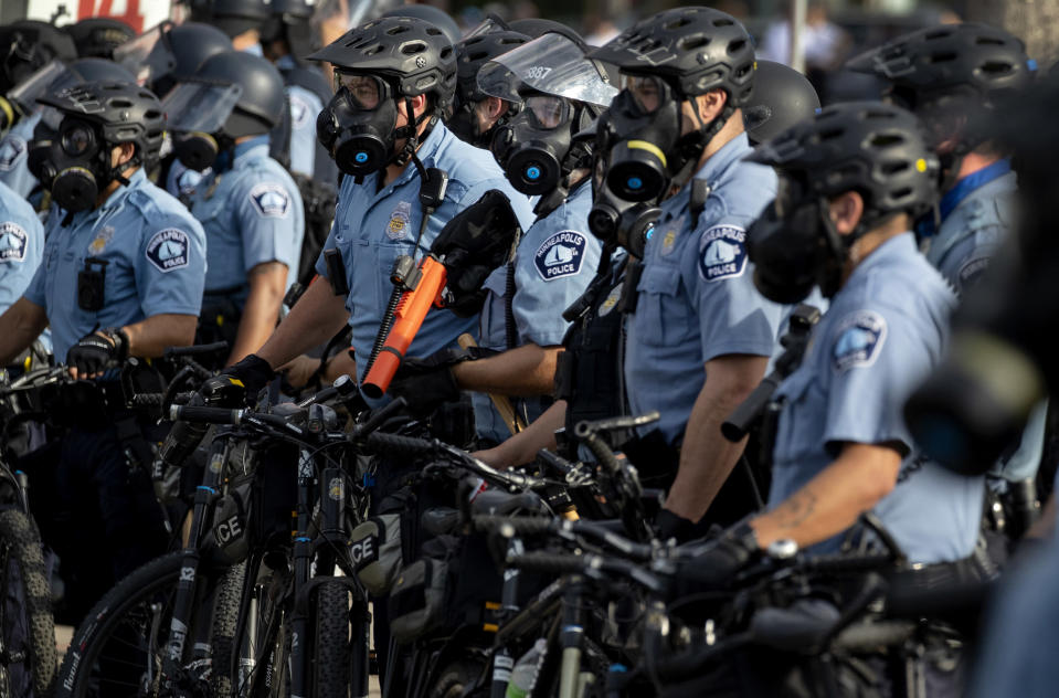 FILE - In this May 27, 2020, file photo, police gather en masse as protests continue at the Minneapolis 3rd Police Precinct in Minneapolis. More than 150 Minneapolis police officers have started the process of filing for disability claims since the death of George Floyd and the ensuing unrest in the city, with the majority citing post-traumatic stress disorder as the reason for their planned departure, according to an attorney representing the officers. (Carlos Gonzalez/Star Tribune via AP, File)