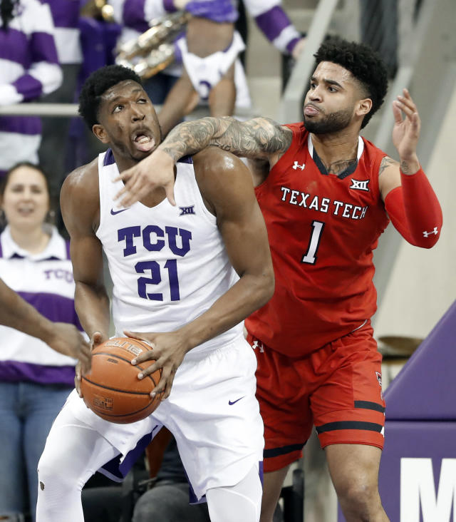 Texas Tech forward Khavon Moore (21) takes a forearm across the face as he works for a shot against Texas Tech guard Brandone Francis (1) in the first half of an NCAA college basketball game in Fort Worth, Texas, Saturday, March 2, 2019. (AP Photo/Tony Gutierrez)