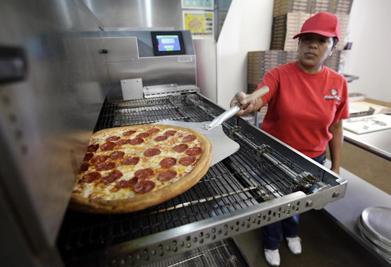FILE - In this Thursday, May 24, 2012, file photo, employee Rosy Tirado pulls a pepperoni pizza from an oven at a Pizza Patron Dallas, Texas. While lower-wage American workers have accounted for the lion's share of the jobs created since the 2007-2009 Great Recession, a survey released March 2013 shows that they are also among the most pessimistic about their future career prospects, their job security and their finances. (AP Photo/Tony Gutierrez)