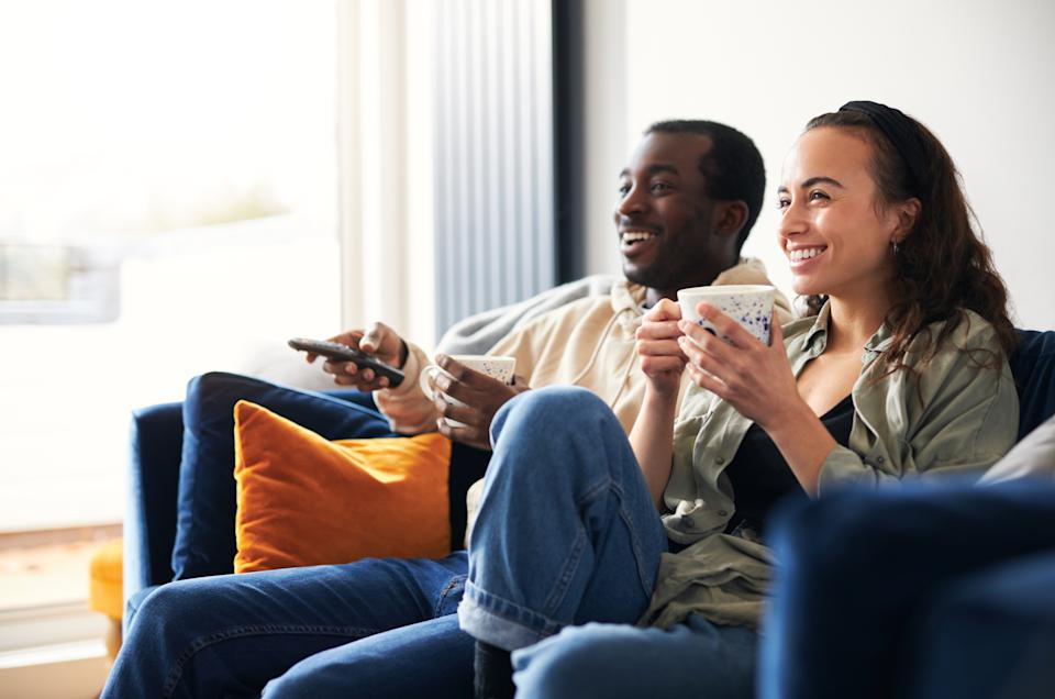 Young couple relaxing on sofa at home watching or streaming tv together