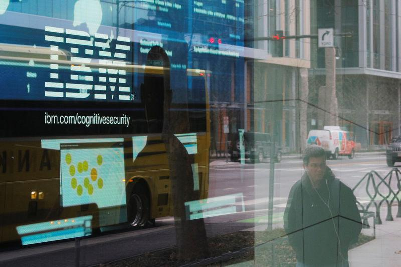 Pedestrians pass a video advertisement for IBM at their office in Cambridge