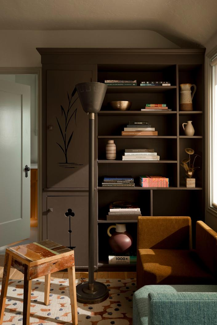 """The casing for the home's original Murphy bed was repurposed as a bookcase for McGriff's office. He explains, """"Some of that detailing on the door isn't what I would have chosen myself, but much like the exterior green and the log cabin interior veneer, it's another detail that we fell in love with right away."""" It is joined by a Piet Hein Eek stool, an Atelier Fevrier rug, a vintage floor lamp, and a Lazzarini Pickering love seat."""